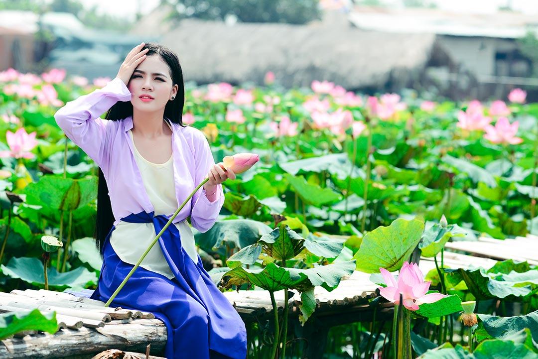 Femme cueillant une fleur lotus